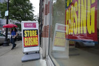 A passer-by walks past a business storefront with store closing signs, Wednesday, Sept. 2, 2020, in Boston. The Congressional Budget Office has warned that the government this year will run the largest budget deficit, as a share of the economy, since 1945, the year World War II ended. Next year, the federal debt — made up of the year-after-year gush of annual deficits — is forecast to exceed the size of the entire American economy for the first time since 1946. (AP Photo/Steven Senne)