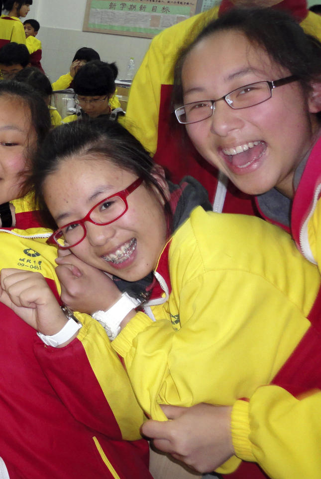 In this undated photo made available Monday, July 8, 2013, Ye Mengyuan, left, and Wang Linjia, right, pose for photos with other classmates in the classroom in Jiangshan city in eastern China's Zhejiang province. Chinese state media and Asiana Airlines have identified the two victims of the Asiana Airlines crash at San Francisco International Airport girls as Ye Mengyuan and Wang Linjia, students in Zhejiang, an affluent coastal province in eastern China. (AP Photo) CHINA OUT