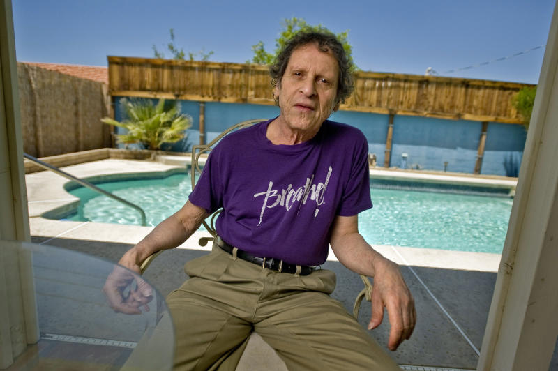 FILE - In this May 7, 2009, file photo, author, comedian and co-founder of the Yippie party as well as stand-up satirist, Paul Krassner, 77, poses for a photo at his home in Desert Hot Springs, Calif. Krassner, the publisher, author and radical political activist on the front lines of 1960s counterculture who helped tie together his loose-knit prankster group by naming them the Yippies, has died. His daughter, Holly Krassner Dawson, says Krassner died Sunday, July 21, 2019, at his home in Desert Hot Springs, Calif. He was 87. (AP Photo/Eric Reed, File)