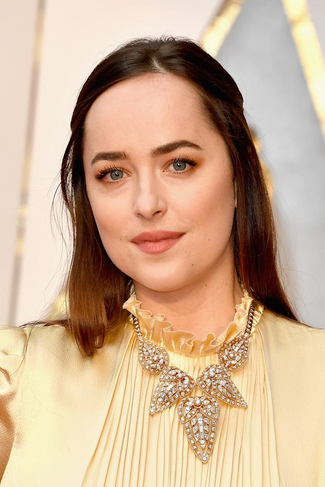 """<p>The <em>Fifty Shades Darker </em>actress accessorized her gold Gucci dress with a diamond statement necklace fromCartier Paris's archive collectionin Geneva.""""We loved it from the start,"""" Johnson's stylist, Kate Young, told <a rel=""""nofollow"""" href=""""http://www.vogue.com/article/dakota-johnson-oscars-2017-red-carpet-dress-gucci"""">Vogue</a>of the look. """"But the jewelry blew us away!"""" (Photo: WireImage) </p>"""