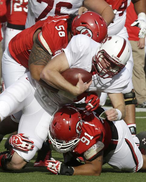 Stanford quarterback Kevin Hogan, center, is tackled by Utah's LT Tuipulotu (58) and teammate Tenny Palepoi (91) during the first quarter of an NCAA college football game on Saturday, Oct. 12, 2013, in Salt Lake City. (AP Photo/Rick Bowmer)