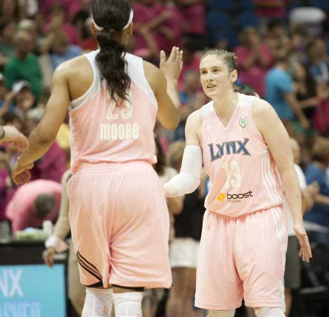 Minnesota Lynx's Lindsay Whalen (13) celebrates with teammate Maya Moore (23) after they defeated the Indiana Fever 84-77 during a WNBA basketball game on Saturday, Aug. 24, 2013, in Minneapolis. (AP Photo/Paul Battaglia)