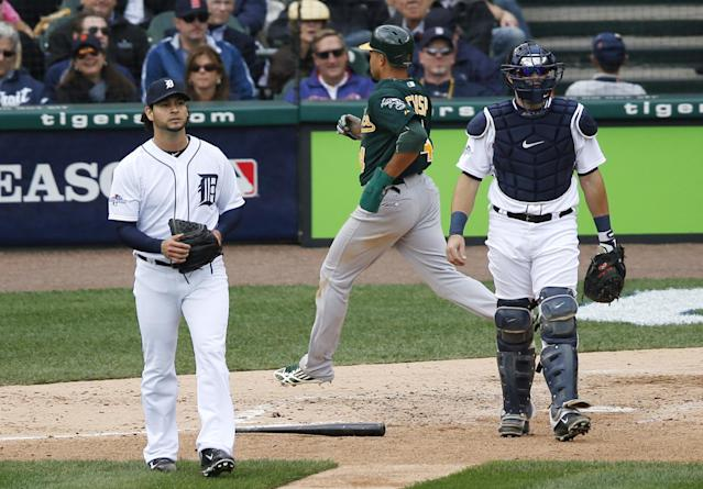 Detroit Tigers pitcher Anibal Sanchez, left, and catcher Alex Avila walk around home plate as Oakland Athletics' Coco Crisp scores during the third inning of Game 3 of an American League baseball division series in Detroit, Monday, Oct. 7, 2013. (AP Photo/Charles Rex Arbogast)