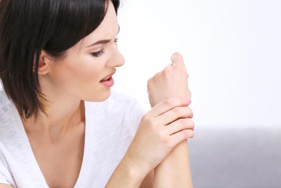 woman suffering from pain in wrist at home.