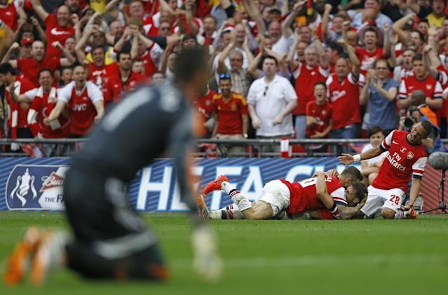 Arsenal's Aaron Ramsey, bottom centre, celebrates after scoring his sides 3rd goal during the English FA Cup final soccer match between Arsenal and Hull City at Wembley Stadium in London, Saturday, May 17, 2014. (AP Photo/Kirsty Wigglesworth)
