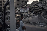 Palestinians look at the rubble of a building that collapsed after it was hit by airstrikes during an 11-day war between Gaza's Hamas rulers and Israel, in Gaza City, Tuesday, June 1, 2021. (AP Photo/Felipe Dana)