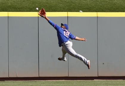 Mets center fielder Juan Lagares can't quite reach a fly ball from Reds third baseman Jack Hannahan. (USA Today)