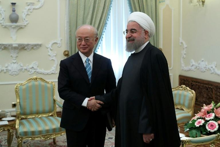 """Iran praised the """"professional performance"""" of the head of the UN atomic energy Yukiya Amano seen in this December 2016 picture with Iranian President Hassan Rouhani during a visit to Tehran"""