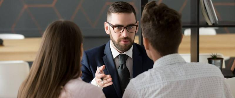 Serious financial advisor in suit and glasses talking to young couple