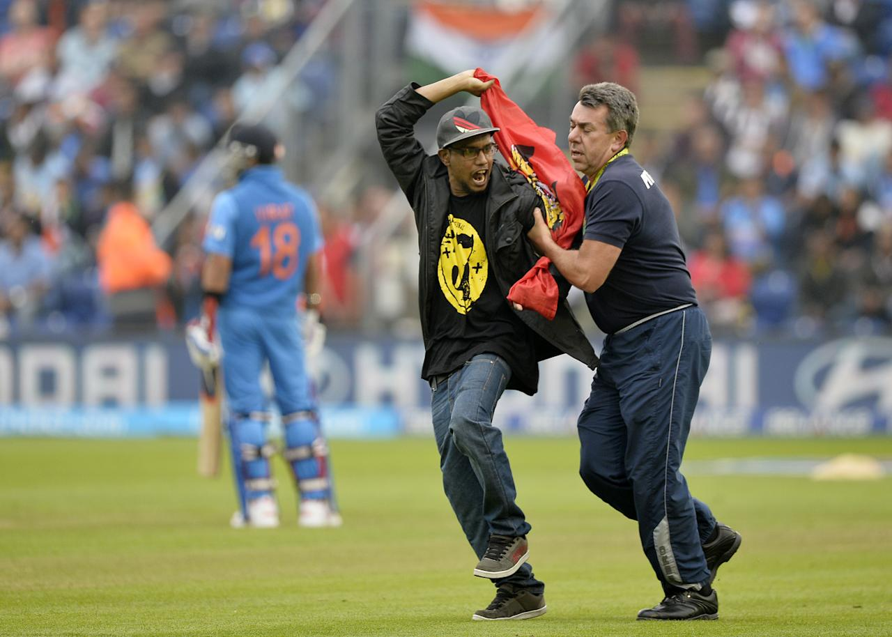 A groundsman removes a demonstrator who ran onto the pitch during the 2013 ICC Champions Trophy semi-final cricket match between India and Sri Lanka at the Cardiff Wales Stadium in Cardiff, south Wales, on June 20, 2013. AFP PHOTO/ADRIAN DENNIS
