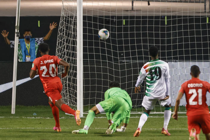 Canada's Jonathan David (20) scores past Suriname's Warner Hahn, second from left, during the second half of a World Cup 2022 Group B qualifying soccer match Tuesday, June 8, 2021, in Bridgeview, Ill. (AP Photo/Kamil Krzaczynski)