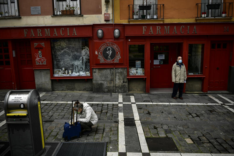 A man stands outside of a pharmacy wearing face protection during confinement to prevent the spread of coronavirus COVID-19, in Pamplona, northern Spain, Wednesday, April 8, 2020. COVID-19 causes mild or moderate symptoms for most people, but for some, especially older adults and people with existing health problems, it can cause more severe illness or death. (AP Photo/Alvaro Barrientos)