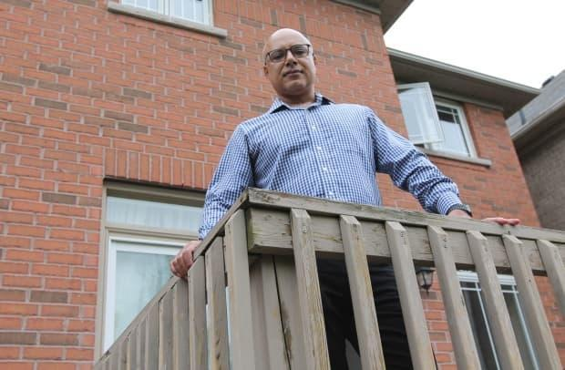 Afshin Livar is shown on the back deck of a house he rents north of Toronto. He says he had to enter into multiple bidding wars to find a home for his family, which left him feeling 'devastated and desperate.'  (James Dunne/CBC - image credit)