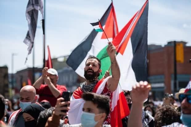 A man waves a Palestinian flag at Saturday's rally. Police say between 2,000 and 3,000 people attended.