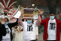 Demonstrators raise their hand as they attend a peace walk honoring the life of police shooting victim 13-year-old Adam Toledo, Sunday, April 18, 2021, in Chicago's Little Village neighborhood. (AP Photo/Shafkat Anowar)