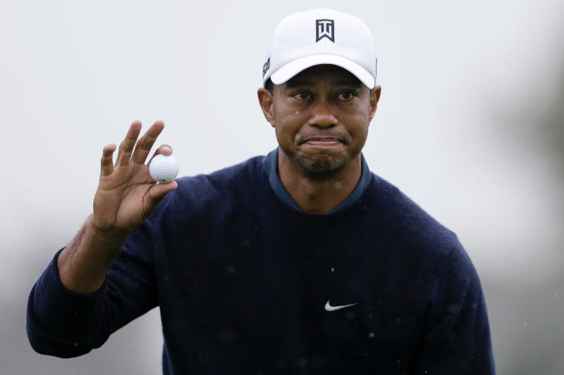 Tiger Woods picks up his ball after finishing his round on the north course at Torrey Pines Golf Course during the second round of the Farmers Insurance Open golf tournament Friday, Jan. 25, 2013, in San Diego. (AP Photo/Gregory Bull)