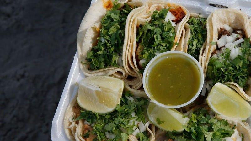 To-go tacos with wedges of lime and a small cup of green sauce