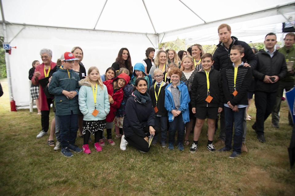 <p>The Duke and Duchess of Sussex posed for a school photo-style picture with a group of children at Abel Tasman National Park on the South Island of New Zealand. </p>