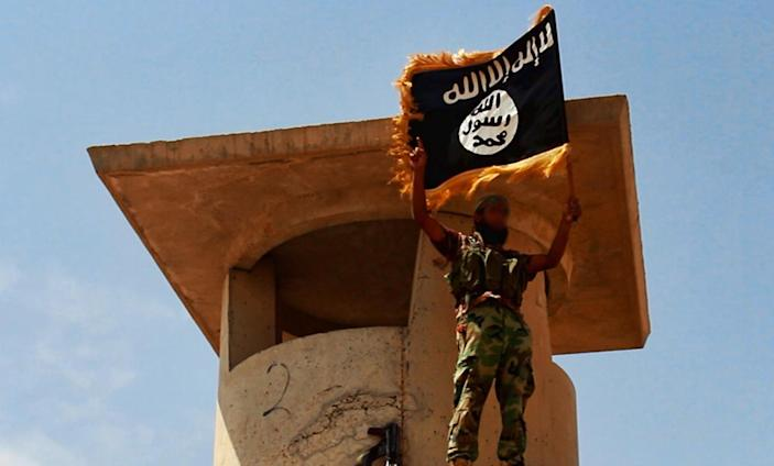 A militant of the Islamic State of Iraq and the Levant (ISIL) poses with the trademark Islamists flag after they allegedly seized an Iraqi army checkpoint in the northern province of Salahuddin on June 11, 2014 (AFP Photo/-)