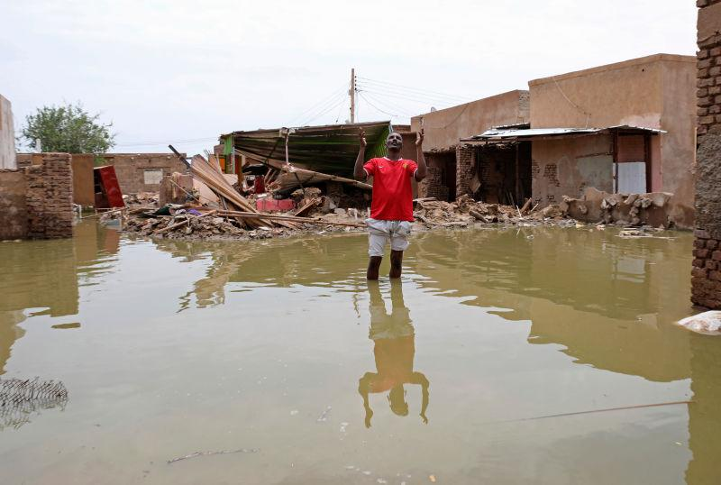 A man gestures as he wades through a flooded road in the town of Salmaniya, about 25 miles (35 km) southwest of the capital, Khartoum, Sudan, Thursday, Sept. 17, 2020.