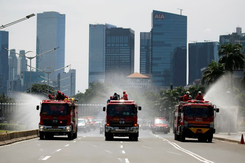 Firefighters spray disinfectant using high pressure pump trucks to prevent the spread of coronavirus disease (COVID-19), on the main road in Jakarta