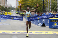Diana Kipyogei, of Kenya, hits the tape to win the women's division of the 125th Boston Marathon on Monday, Oct. 11, 2021, in Boston. (AP Photo/Winslow Townson)