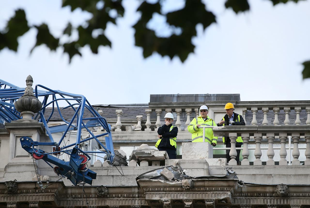 Engineers look at the damage as a crane working on redevelopment at the Cabinet Office in Whitehall, near to Downing Street in London, was brought down by high winds, Monday, Oct. 28, 2013. A major storm with hurricane-force gusts is lashing southern Britain, parts of France and Netherlands, causing flooding and travel delays with the cancellation of many flights and trains. Weather forecasters say it is one of the worst storms to hit Britain in years. (AP Photo/Alastair Grant)