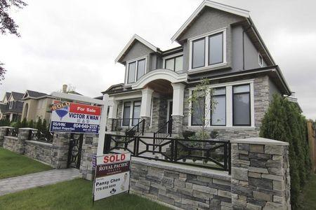 FILE PHOTO - Realtors' signs are hung outside a newly sold property in a Vancouver neighborhood