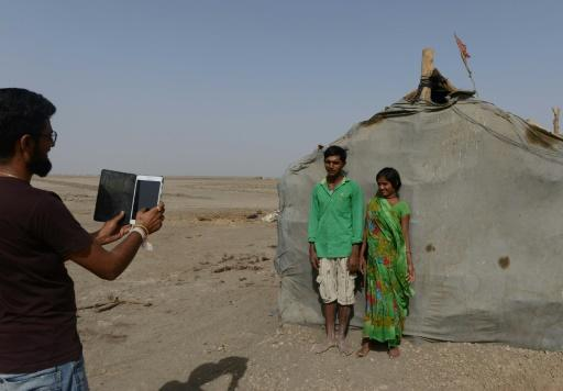 Dhvanit Pandya, coordinador del programa, fotografía con una tableta a los trabajadores de la sal Pradhuman Dilubhai Kansagara (C) y su esposa Kailashben Pradhuman Kansagara, el 7 de abril de 2017 en Pequeño Rann de Kutch, India-- Sheltered beneath a canvas sheet to escape the blistering desert sun, miles from any roads or power lines, a group of Indian children huddle around a digital tablet and experience the internet for the very first time. The remote wi-fi connection is powered by a van bringing the digital world to around 10,000 families living on the inhospitable salt flats of western Gujarat, where they work eight months a year in extreme conditions. (AFP | Sam Panthaky)