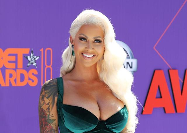<p>Amber Rose wears bleached blonde soft waves that pop against her emerald green dress. (Photo: Getty Images) </p>