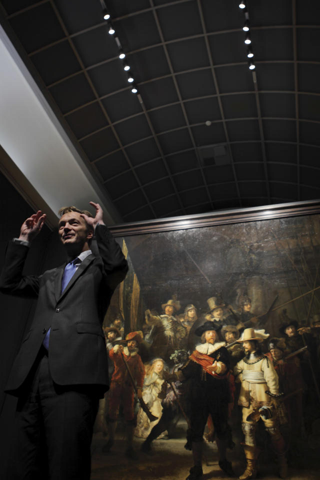"EXPANDS ORIGINAL CAPTION -- Director Wim Pijbes of the national Rijksmuseum, left, gestures talking about the newly installed LED lights, top, illuminating Rembrandt's ""Night Watch"", rear, in Amsterdam, Netherlands, Wednesday Oct. 26, 2011. The ""Night Watch"" may need a different nickname after the painting has been put under new lighting that makes it look like a day scene. The change is startling, as characters once barely visible now stand out in vivid color. The 1642 painting was commissioned for one of Amsterdam's citizen militias and is officially titled ""The Company of Frans Banning Cocq."" Pijbes said Wednesday the painting , widely considered Rembrandt's greatest masterpiece, may in fact only have acquired the ""Night Watch"" name due to a dark varnish that was removed decades ago. He said the new LED lighting system custom designed by Philips mimicks daylight, helping return the work to its original dynamic, colorful appearance. (AP Photo/Peter Dejong)"