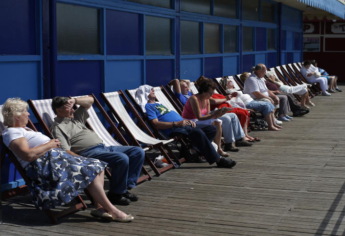 People sit in the sun on deck chairs at Central Pier in Blackpool, northern England July 24, 2013. British beach resorts, which flourished in the 19th century and earlier, have tempted tourists for years with amusement arcades, fairground rides and cheap and cheerful souvenirs. However, as a 2013 report by the Centre for Social Justice states, many seaside towns suffered as from the 1970s it became cheaper and easier for British tourists to travel abroad. Now, according to the Office for National Statistics, larger seaside towns in England suffer from higher-than-average levels of deprivation compared to the rest of the country. Nevertheless, they do continue to attract holiday makers. Picture taken July 24, 2013. REUTERS/Phil Noble (BRITAIN - Tags: SOCIETY TRAVEL)
