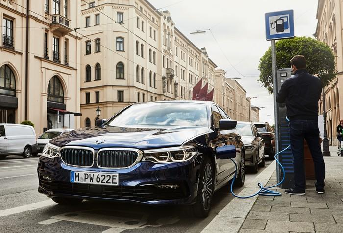 A BMW plug-in hybrid sedan, parked next to a charger on a German city street.