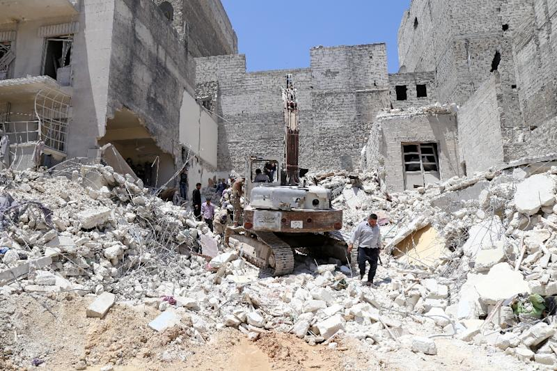 People inspect the rubble of collapsed buildings following a reported airstrike by government forces on May 24, 2015, in the rebel-held al-Sukari neighborhood of the northern city of Aleppo (AFP Photo/Baraa Al-Halabi)