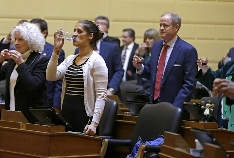 "Rhode Island State Rep. Moira Walsh, second from left, drinks from a water bottle while others raise glasses of wine in honor of St. Joseph's Day, in the House Chambers at the Rhode Island Statehouse, Thursday, March 16, 2017, in Providence. The toast was a part of Irish and Italian cultural celebrations held in the legislative chambers. Walsh last week said that there's an ""insane amount of drinking"" in the building. Legislative leaders have disputed that. (AP Photo/Elise Amendola)"