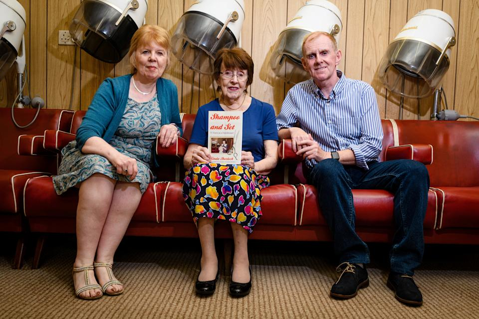Linda, Margaret and Adrian Sherlock inside the hairdressers with the book written by Linda. (SWNS)