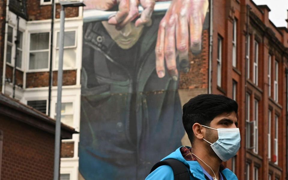 A man walks past a mural in Manchester - Oli Scarff/AFP
