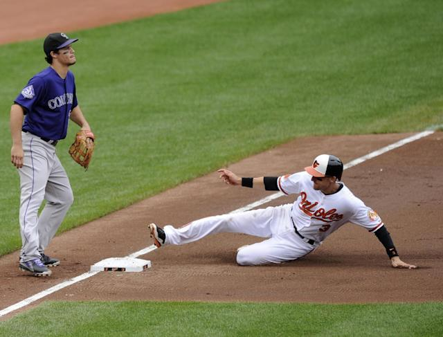 Baltimore Orioles' Ryan Flaherty (3) slides into third against Colorado Rockies third baseman Nolan Arenado, left, on a single by Alexi Casilla during the second inning of a baseball game on Sunday, Aug. 18, 2013, in Baltimore. (AP Photo/Nick Wass)