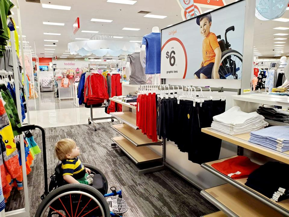 Ollie Garza-Pena, 2, sits in a wheelchair in Target. He's looking at an advertisement featuring a boy also in a wheelchair.