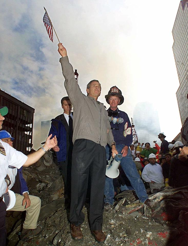 As rescue efforts continue in the rubble of the World Trade Center in New York, President Bush raises an American flag while standing on a burnt fire truck in front of the World Trade Center during a tour of the devastation, Friday, Sept. 14, 2001. Firefighter Bob Beckwith is at right. Accompanied by New York Mayor Rudolph Giuliani and other New York politicians, Bush toured the disaster site on foot after getting a helicopter view of the devastation. (AP Photo/Doug Mills)