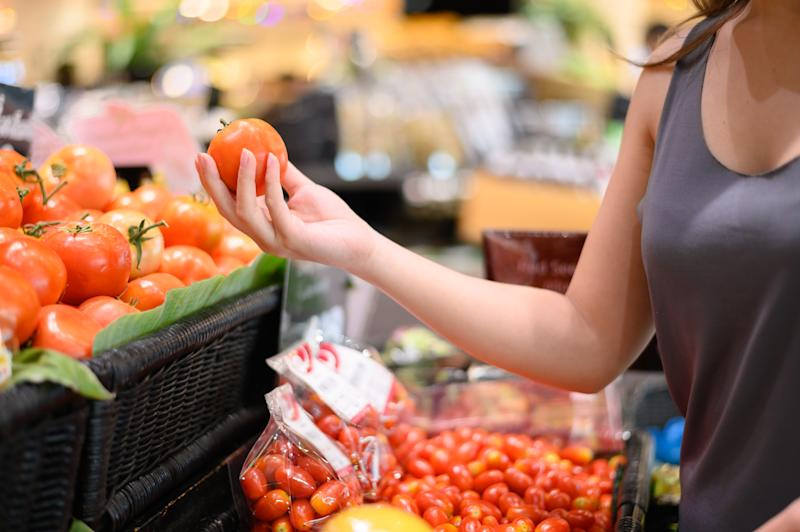 Young woman picking up tomato at grocery store or supermarket against coronavirus precautions