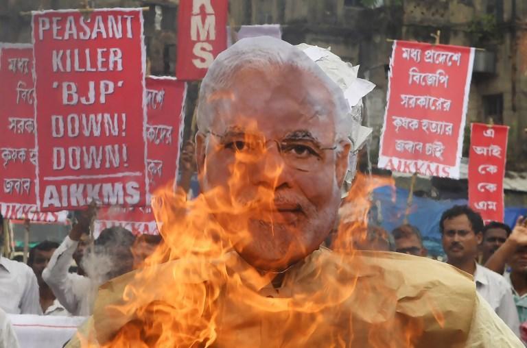 <p>Indian farmers and social activists burn an effigy of Prime Minister Narendra Modi during a protest against the government and over the deaths of farmers in the state of Madhya Pradesh in Kolkata on June 19, 2017.<br /> India has nearly 260 million farmers and farm labourers, and agriculture accounts for 17 percent of the country's gross domestic product. But a lack of irrigation facilities and years of erratic monsoon rains have led to a crisis in the sector, with thousands of farmers across the country reportedly killing themselves over crop failures and debt every year. Madhya Pradesh is one of several states that have suffered disappointing rains and crop failures in recent years. More than 1,600 farmers killed themselves in the state in 2016, according to official figures. / AFP PHOTO / Dibyangshu SARKAR </p>
