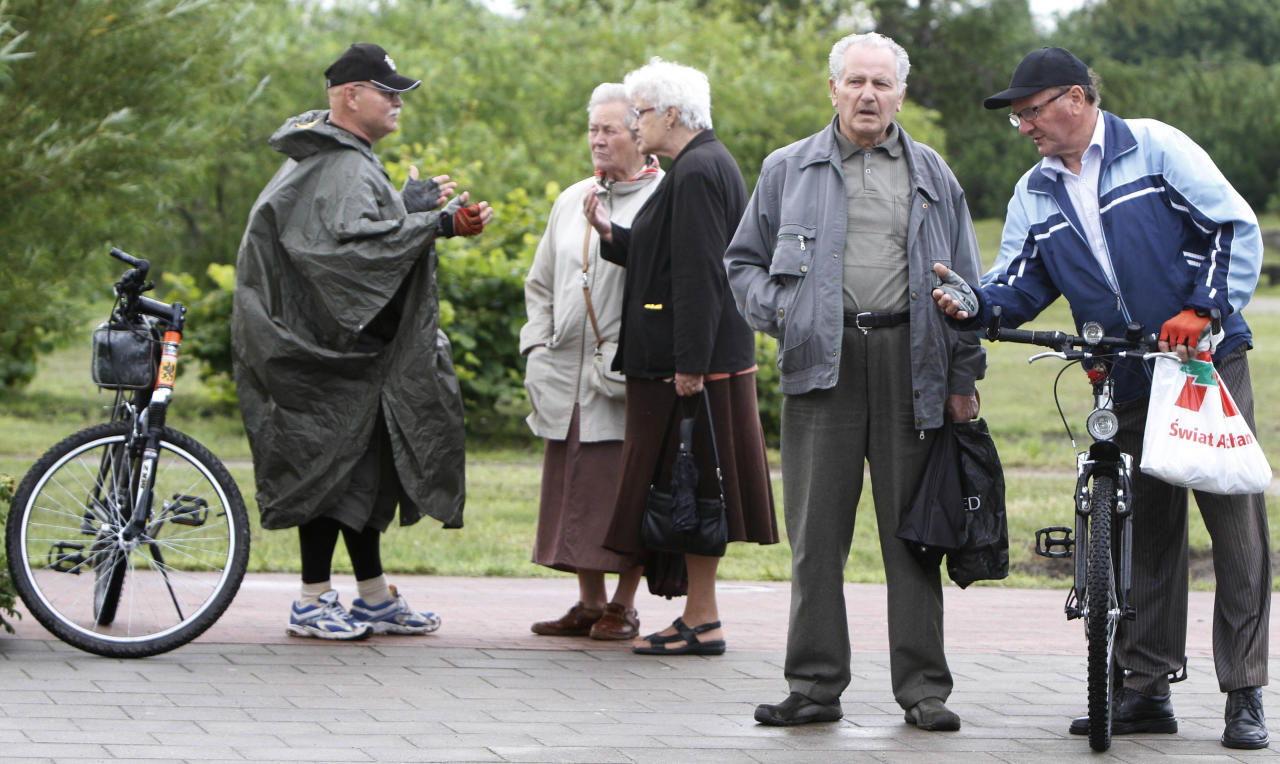 People discuss the new statue of former President Ronald Reagan and Pope John Paul II at its unveiling in Gdansk, Poland, on Saturday, July 14, 2012. The statue honors the two men whom many Poles credit with helping to topple communism. (AP Photo/Czarek Sokolowski)