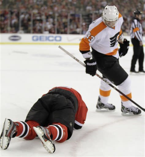 In this Sunday, May 6, 2012, photo, Philadelphia Flyers' Jakub Voracek skates by as New Jersey Devils' Dainius Zubrus lies on the ice after being hit by Flyers' Claude Giroux during the second period of Game 4 of a second-round NHL hockey Stanley Cup playoff series in Newark, N.J. The NHL has suspended Giroux one game for his illegal check to the head on Zubrus. Giroux will miss Game 5 Tuesday night in Philadelphia. (AP Photo/Julio Cortez)