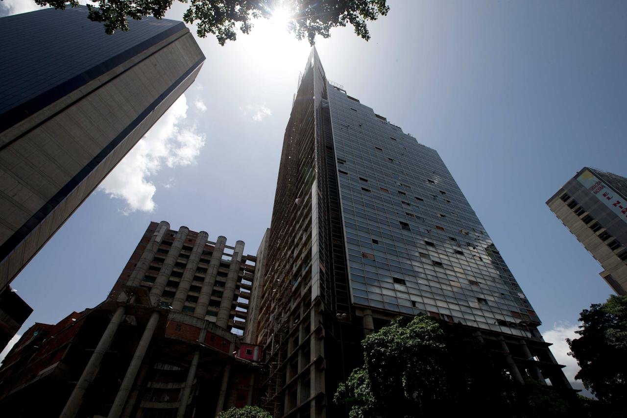 A view of the Tower of David, a building that was abandoned in the 1990s and became the world's tallest slum, the half-built skyscraper was transformed by squatters into a vertical ghetto, in Caracas, Venezuela, Tuesday, July 22, 2014. Officials and armed soldiers began moving out the first of thousands of squatters who have lived for nearly a decade in a soaring, half-built skyscraper in the heart of Caracas. (AP Photo/Fernando Llano)