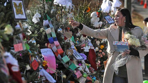 PHOTO: A woman hangs candy canes on the 26 trees near a memorial for the victims of the Sandy Hook Elementary School shooting on Dec. 20, 2012, in Newtown, Conn. (Hartford Courant/TNS via Getty Images, FILE)