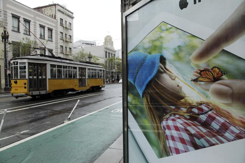 "In this photo taken Thursday, May 3, 2012, an old streetcar passes a display for an Apple iPad near Twitter's new headquarters in San Francisco. With Twitter's new headquarters set to open there soon, residents of a San Francisco neighborhood notorious for crime, drugs and homelessness remain among the least likely to have any way to send a tweet, much less access to basic goods and services. At a recent weekend ""hackathon,"" engineers and entrepreneurs sought ways to use tech to help people in the Tenderloin and Mid-Market Street area find food, housing, healthcare and jobs. In the process, city leaders hope to ease tensions between needy locals and newly arriving startups flush with cash. (AP Photo/Eric Risberg)"