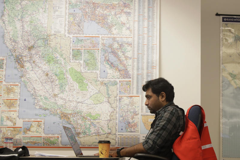 Senior program analyst Siva Jasti works next to a map of California in the Pacific Gas & Electric (PG&E) Emergency Operations Center in San Francisco, Thursday, Oct. 10, 2019. More than 1.5 million people in Northern California were in the dark Thursday, most for a second day, after the state's biggest utility shut off electricity to many areas to prevent its equipment from sparking wildfires as strong winds sweep through. (AP Photo/Jeff Chiu)