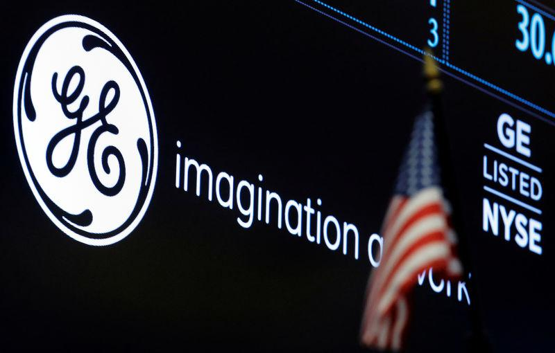 FILE PHOTO: The ticker and logo for General Electric Co. is displayed on a screen at the post where it's traded on the floor of the NYSE
