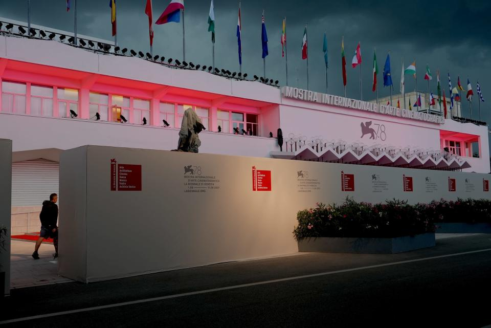 A worker walks by a wall hiding the red carpet of the 78th edition of the Venice Film Festival from the view of the public at the Venice Lido, Italy, TO SEND , Monday, Aug. 30, 2021. (AP Photo/Domenico Stinellis)